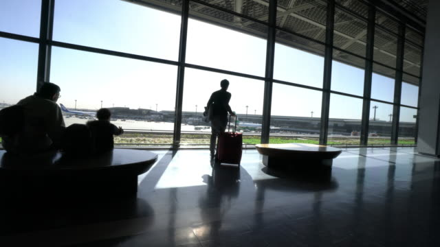 travelers silhouettes at airport - wheeled luggage stock videos and b-roll footage