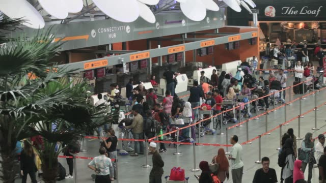 Travelers stand in line in front of AirAsia Bhd checkin counters at Kuala Lumpur International Airport 2 in Sepang Selangor Malaysia on Thursday May...