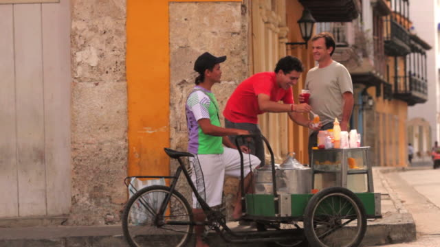 ms travelers talking with local street vendor / cartagena, bolivar, colombia    - colombia stock videos & royalty-free footage