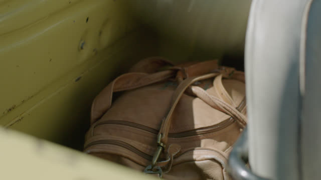 Travelers throw duffel bags in back of classic pick-up