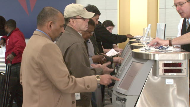 vidéos et rushes de travelers using selfserve kiosk for boarding pass at ronald reagan washington national airport / arlington virginia united states - aéroport ronald reagan