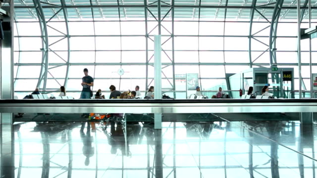travelers waiting in the airport lounge tracking shot - gate stock videos & royalty-free footage