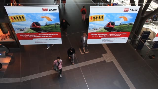 travelers walk along concourse beneath banners displaying deutsche bahn ag ticket prices at berlin central station also known as hauptbahnhof in... - carry on luggage stock videos and b-roll footage