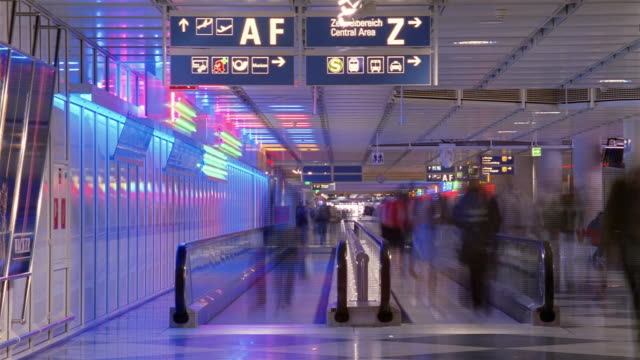 Travelers walk on the moving walkways in the airport terminal in Munich, Germany.