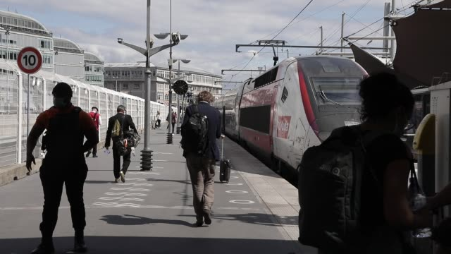 travelers walk on the platform of a station to access the train at gare de lyon train station for vacation departures on july 17, 2020 in paris,... - 高速列車点の映像素材/bロール