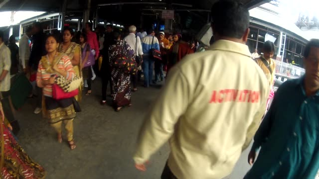 Travelers walk past a family waiting at Howrah Station in Calcutta.