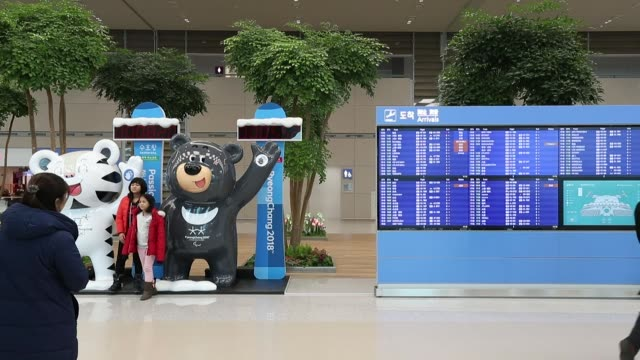 Travelers walk past an advertisement featuring the 2018 PyeongChang Winter Olympic Games mascot Soohorang left and Paralympic Games mascot Bandabi...