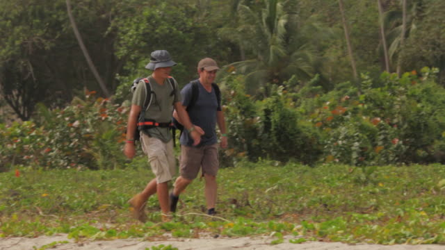 MS TS Travelers walking by tropical forest / Tyrona N. Park, Magdalena, Colombia