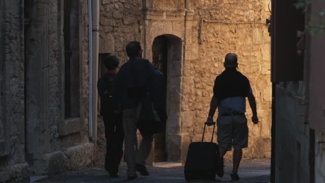 travelers walking down a european street - saignon stock videos & royalty-free footage
