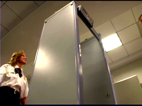 travelers walking through metal detector at airport - metal detector sicurezza video stock e b–roll