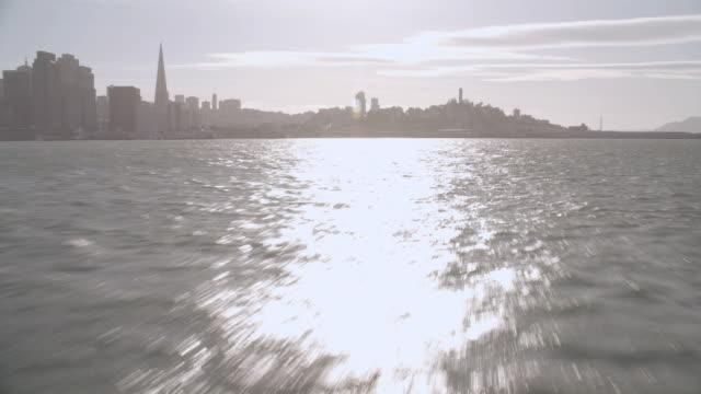 vídeos y material grabado en eventos de stock de aerial traveling across the bay towards telegraph hill under brilliant sun / san francisco, california, united states - torre coit