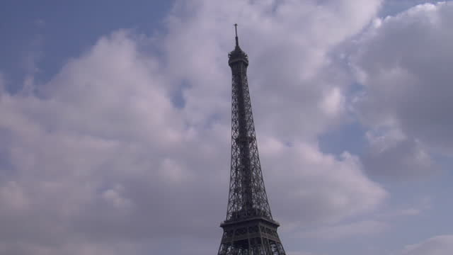 traveling along the seine river under a wrought iron bridge the passerelle debilly revealing the majestic eiffel tower against the sky. - majestic stock videos & royalty-free footage