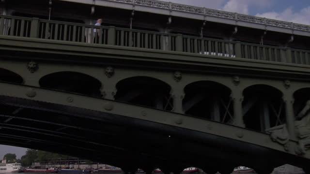 vidéos et rushes de traveling along the seine river viewing the majestic eiffel tower against the sky and passing under the bridge pont de bir-hakeim. - pont de bir hakeim