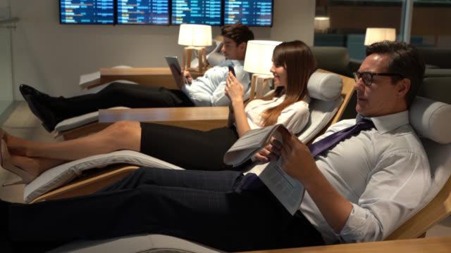 vídeos de stock e filmes b-roll de traveling business people relaxing at the airport's vip lounge - esperar