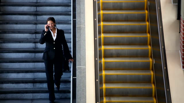 traveling business woman walking on stairs, using cell phone - mixed race person stock videos & royalty-free footage