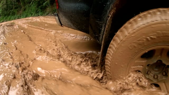 slo mo traveling by four wheel drive car on muddy trail road - mud stock videos and b-roll footage
