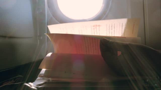 vídeos de stock, filmes e b-roll de viajar de avião: mulheres asiáticas lendo livro - sentando
