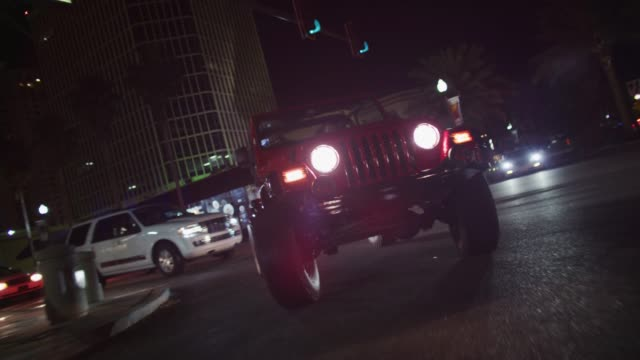 vídeos de stock e filmes b-roll de pov traveling down a city street at night; a jeep makes a right-hand turn at an intersection as it follows camera. - jeep