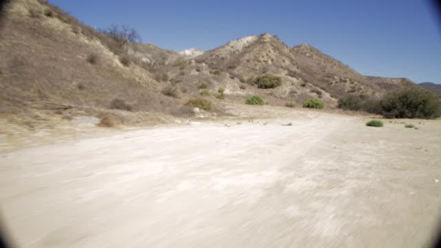 pov traveling down dirt road through rocky mountains / santa clarita, california, united states - santa clarita stock videos & royalty-free footage