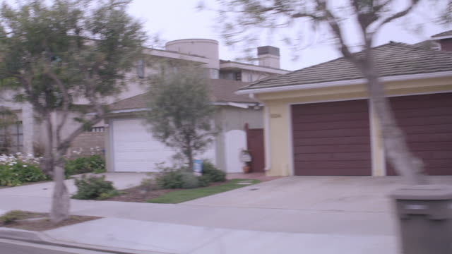 pov traveling down street past two-story contemporary homes in an upscale, suburban neighborhood / los angeles, california, united states - moving process plate stock videos and b-roll footage