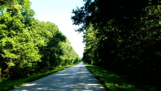 Traveling, driving down a two-lane country road in Texas.