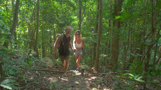 traveling hikers couple age 25-29 yearold of latin american and hispanic ethnicity holding hand enjoying  travel holidays active healthy lifestyle adventure journey vacations at jungle.helping hands concept. - wonderlust stock videos & royalty-free footage