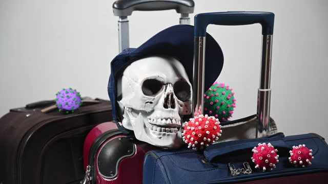 traveling in times of coronavirus can mean the spread of the virus and its mutations and cause the death of many people. skull on suitcase with coronavirus mutations. - westernisation stock videos & royalty-free footage