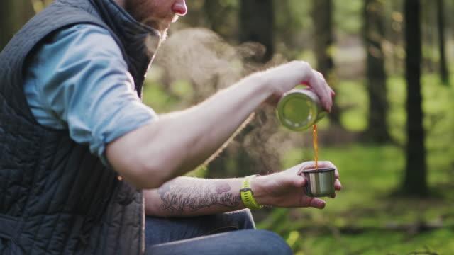 traveling man vandring genom en tallskog sitter ner för att dricka lite kaffe - coffee drink bildbanksvideor och videomaterial från bakom kulisserna