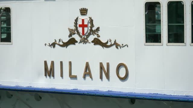 traveling on a ferry with milano sign in a luxury resort town near lake como, italy, europe. - slow motion - barca a motore video stock e b–roll