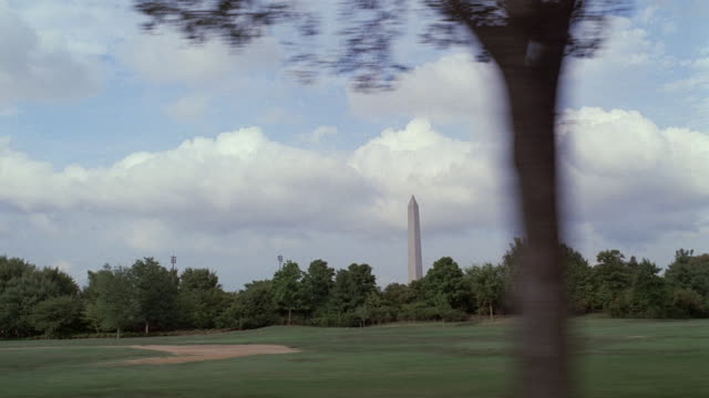 vídeos y material grabado en eventos de stock de pov traveling past the washington monument visible through the trees / washington, district of columbia, united states - pasear en coche sin destino