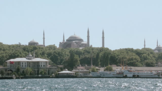 pov traveling past waterfront properties and ferry boat with the hagia sophia in the distance / istanbul, turkey - vagare senza meta video stock e b–roll