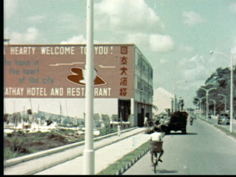 1957 MONTAGE Traveling shot down city street + past cricket match / Singapore / AUDIO