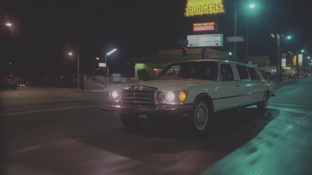 traveling shot leading white mercedes limo thru n-d city streets - night - limousine stock videos & royalty-free footage