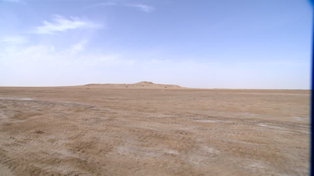 traveling shot showing the plain of eridu and the archaeological tell. eridu was the earliest city in mesopotamia and arguably the first in history. - desert stock videos & royalty-free footage