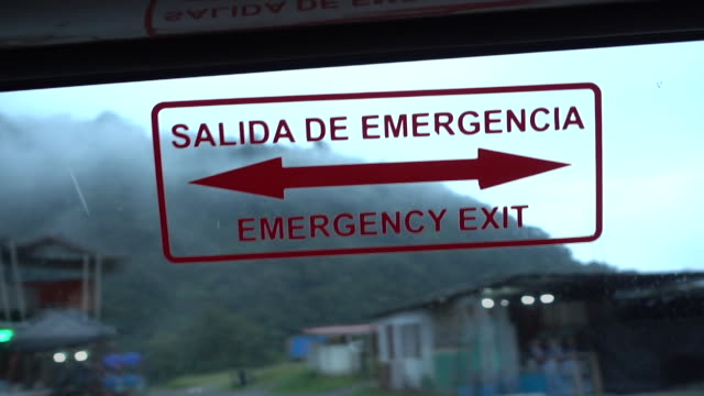 stockvideo's en b-roll-footage met traveling through the amazon forest by bus to tena ecuador on my way to the city of tena i filmed this emergency sign showing the the path to my... - informatiebord