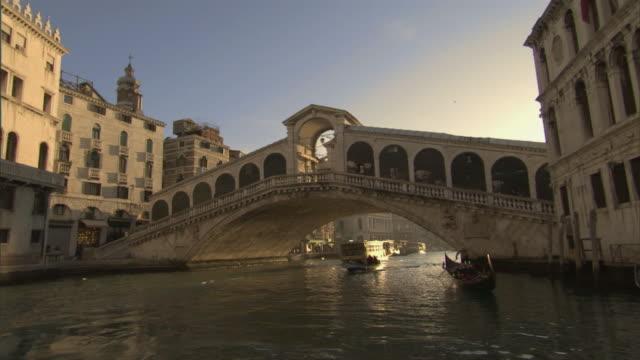 vídeos y material grabado en eventos de stock de ws pov traveling towards and under rialto bridge past buildings lining canal / venice, veneto, italy - puente de rialto
