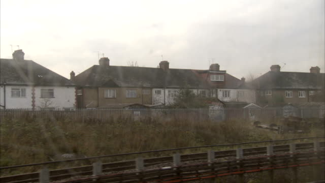 a traveling tube train passes streets of houses in a london suburb. available in hd. - suburban stock videos & royalty-free footage