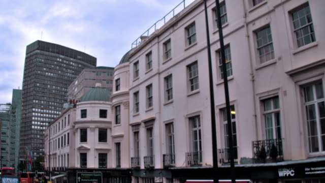 Traveling view of buildings along streets in London, England.