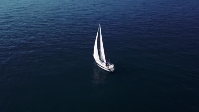 vídeos de stock, filmes e b-roll de viajando com um veleiro, velejar ao longo dos mares - velejar