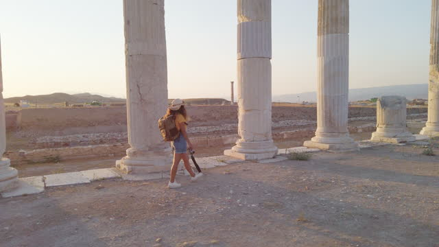 traveller tourist photographer girl is walking behind the columns holding a camera in ancient ruins of laodicea on the lycus at sunset, pamukkale - greece stock videos & royalty-free footage