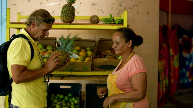 A traveller with local vendors on a Caribbean market