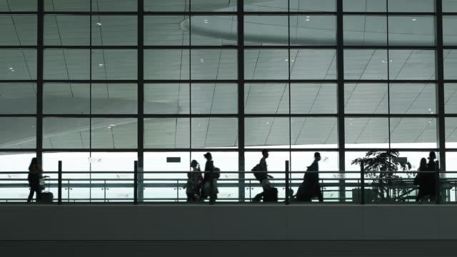 vidéos et rushes de gens du voyage à pied à l'aéroport - salle d'embarquement
