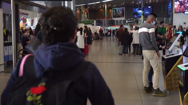 travellers wearing face masks at bogota's el dorado airport in bogota, colombia. - flugpassagier stock-videos und b-roll-filmmaterial