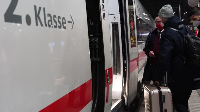 vídeos y material grabado en eventos de stock de travellers wearing protective face masks pulling suitcases prepare to board an arriving ice high-speed train of german state rail carrier deutsche... - centro de berlín