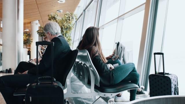 stockvideo's en b-roll-footage met reizigers met bagage te wachten op de luchthaven - spelletjesavond
