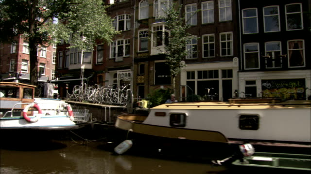Travelling along a canal, passing moored boats. Available in HD.