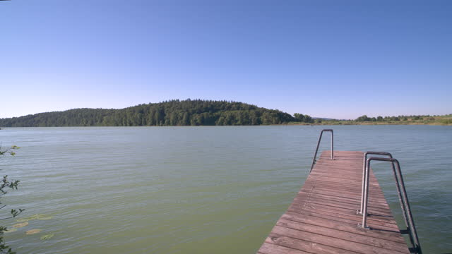 travelling along a small pier on a lake on a sunny day - small stock videos & royalty-free footage