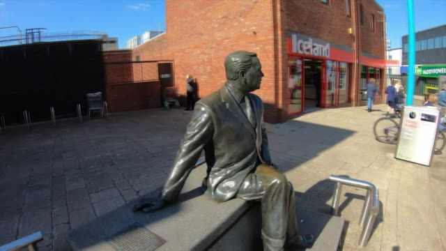 Travelling shot around statue for former British Prime Minister Harold Wilson in Knowsley Merseyside