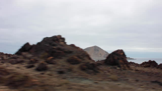 travelling shot , by morning, from a car, of cerro soldado and pan de azucar island. there are many rocks everywhere. the perspective is as seeing... - atacama region stock videos & royalty-free footage