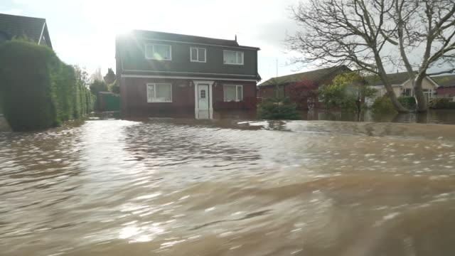 travelling shot through village of fishlake in doncaster, showing the extent of the flooding - village stock videos & royalty-free footage